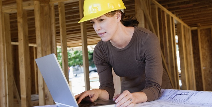 Woman Looking at Laptop at Building Site